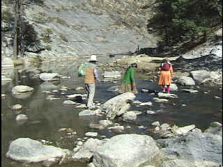 Melina and her family crossing the river at the valley bottom.